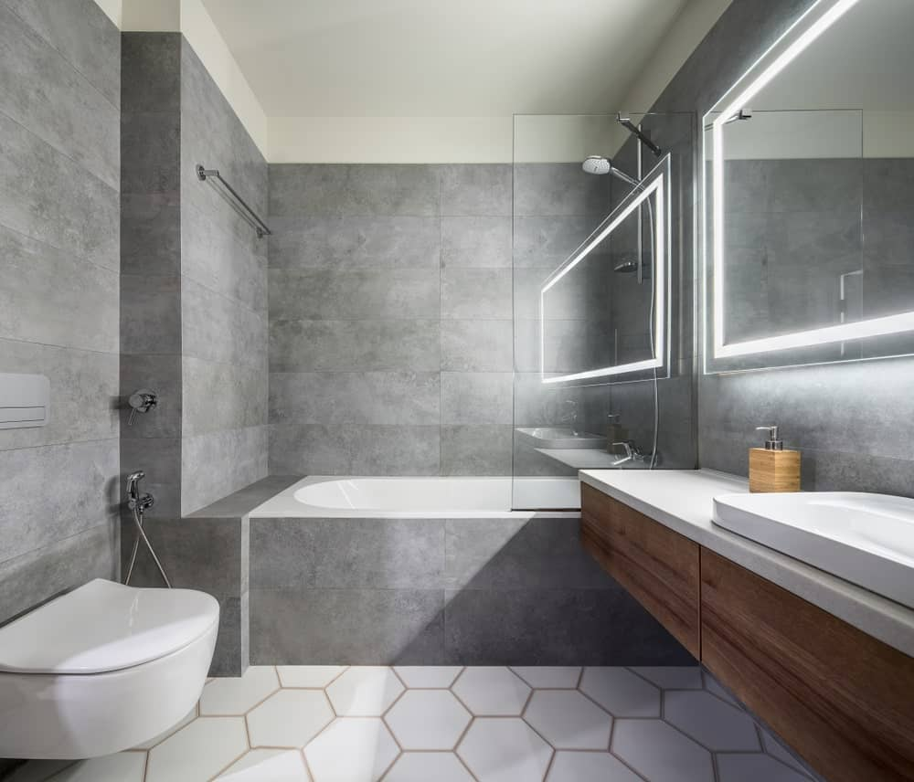 Full bathroom with modern interior design featuring white hex flooring, gray tiled walls, wall-hung toilet, shower and tub combo and a floating sink vanity paired with a luminous mirror.