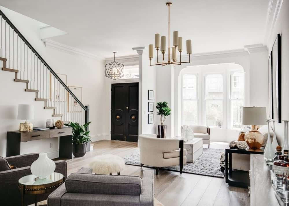 An elegant living room with hardwood floors, white walls and a white ceiling. The area features a set of modish furniture along with a charming chandelier ceiling light.