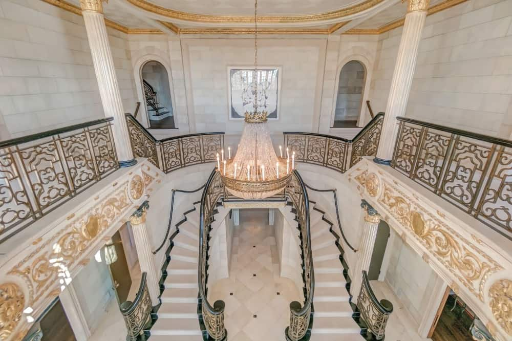 The view of the grand foyer from the second floor, boasting its glamorous grand chandelier along with the elegant staircase and wall designs. Images courtesy of Toptenrealestatedeals.com.