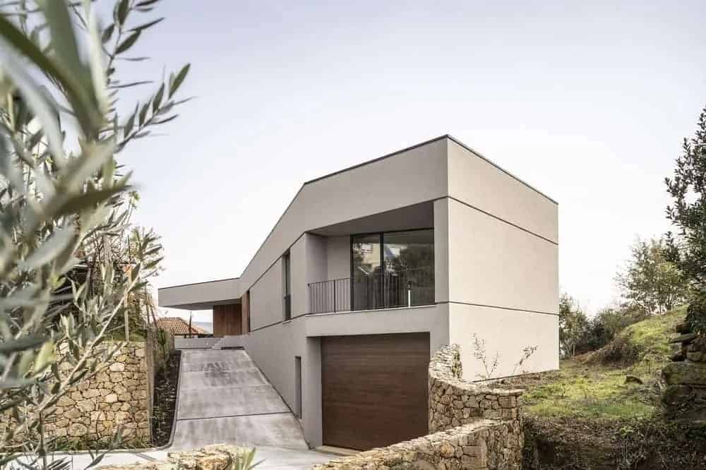 This wonderful modern villa has an irregular geometric shape that follows the lay of the hilly land. It has a warm gray exterior wall tone partnered with the dark brown garage door and walls of the main entrance makes for a unique look surrounded by stone walls and concrete driveway.