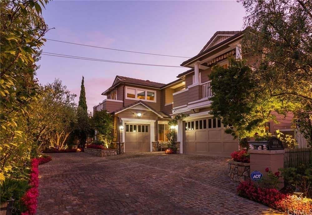 This grand home has a warm look to its exteriors that has different shades of earthy tones that totally work well with the stone driveway leading to the home. This driveway is surrounded by colorful flowering shrubs, stone planters and tall trees all illuminated by the warm yellow outdoor lights.