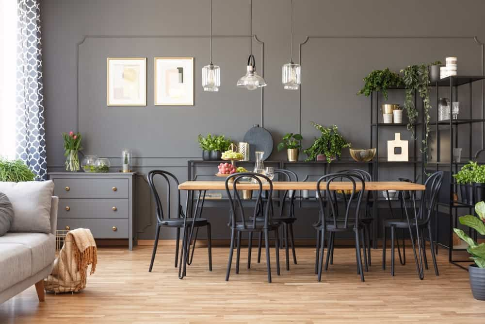 Gray dining room with wainscoted walls, hardwood flooring, wooden dining table surrounded by black round back chairs, metal shelvings, glass pendants, artworks and small potted plants.