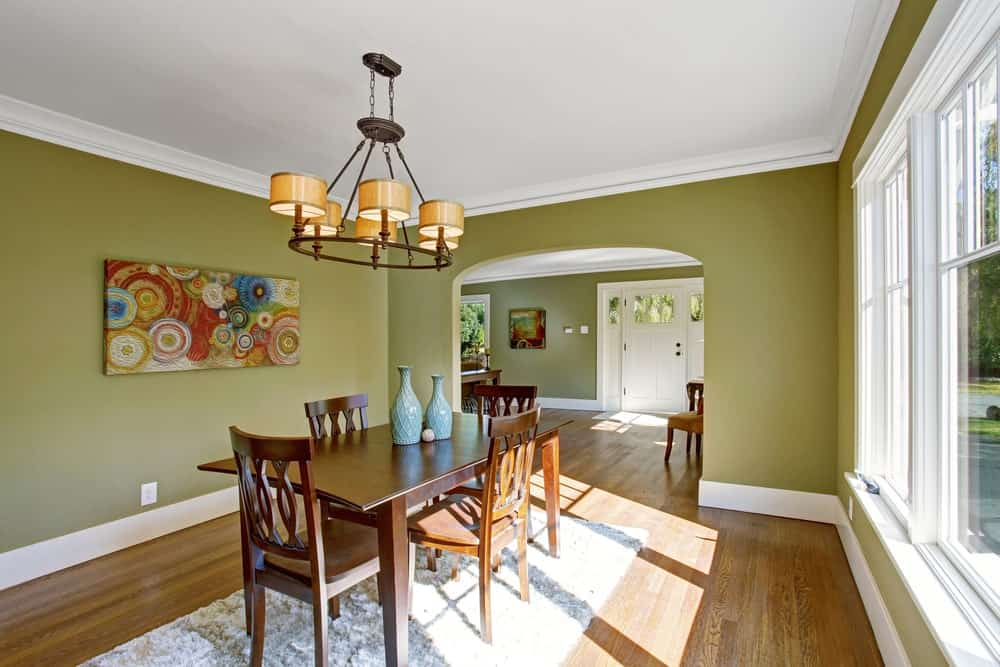 Green Dining room with hardwood flooring, white framed windows, colorful artwork, wooden dining set over a textured rug and a round chandelier.