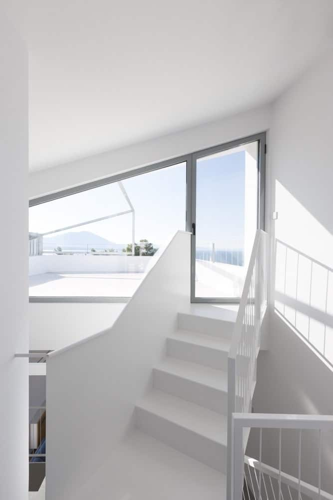 Staircase leading out to the rooftop in the Hidden Cross Residence designed by Ntovros Vasileios Architects.