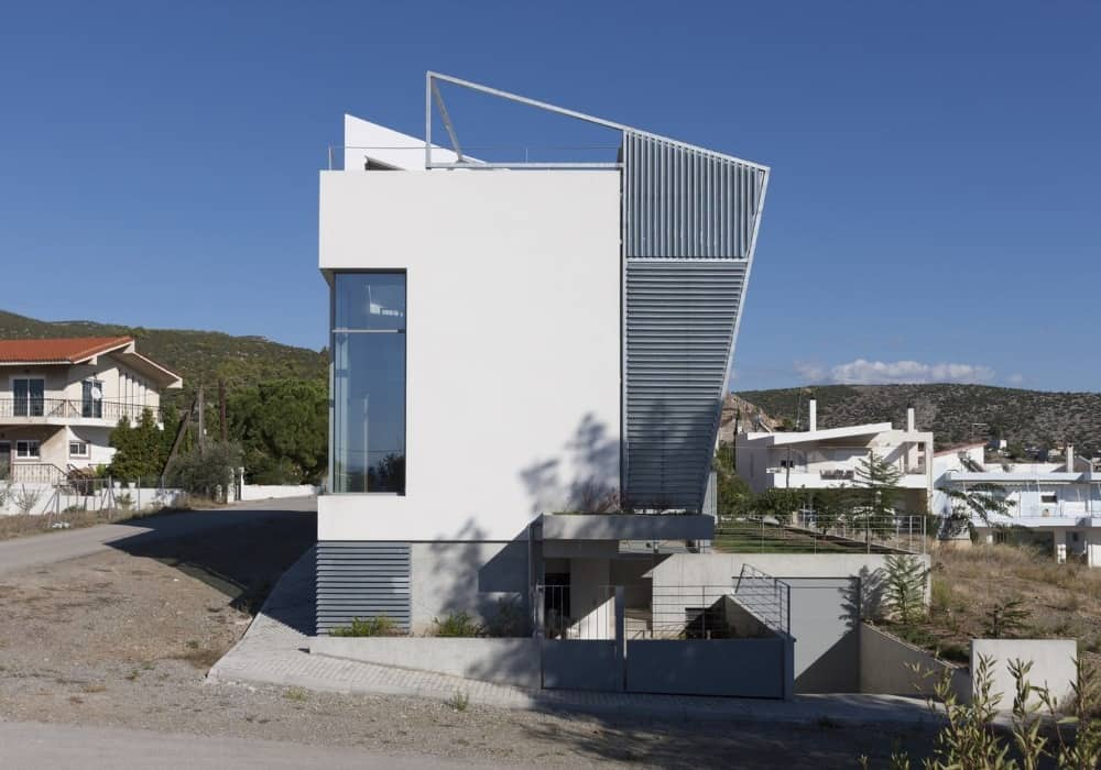 House side exterior of the Hidden Cross Residence designed by Ntovros Vasileios Architects.