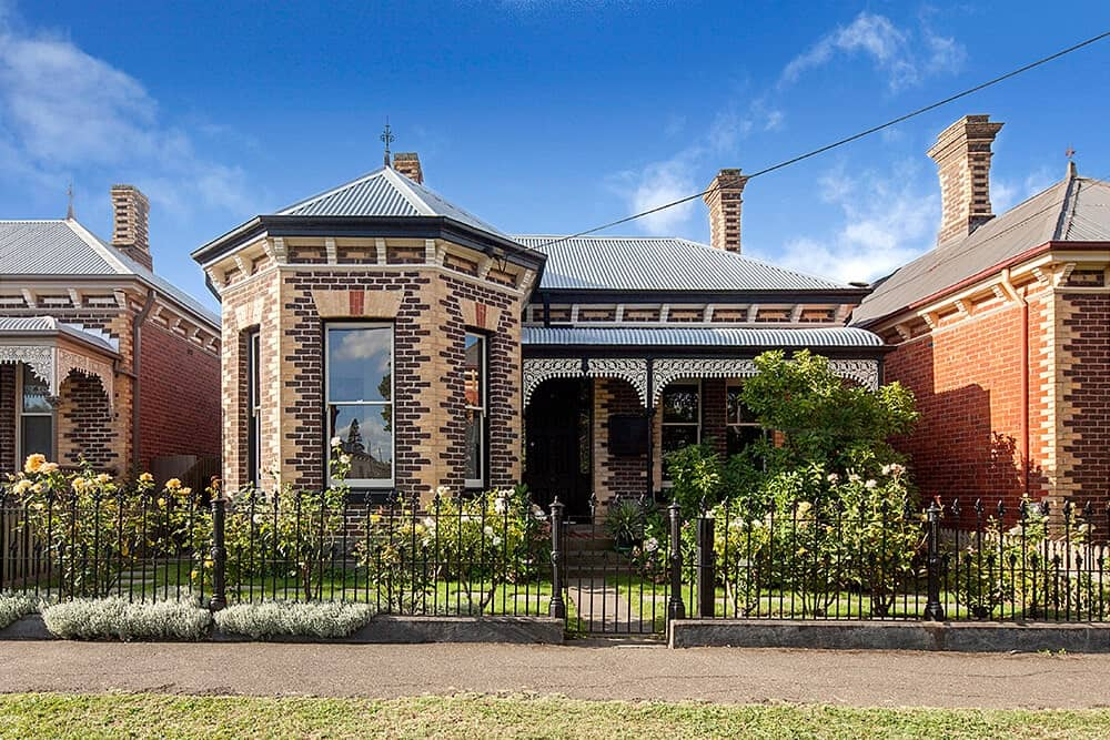A charming contemporary house with Victorian architecture enclosed in an ornate wrought iron fence. It features beautiful brick walls, glazed windows and stone paving.