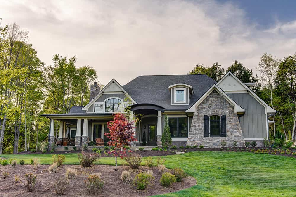 Contemporary house with rustic touches from the stone facade and chimney. It includes a portico, tinted glazed windows and serene landscaping with towering trees as its backdrop.