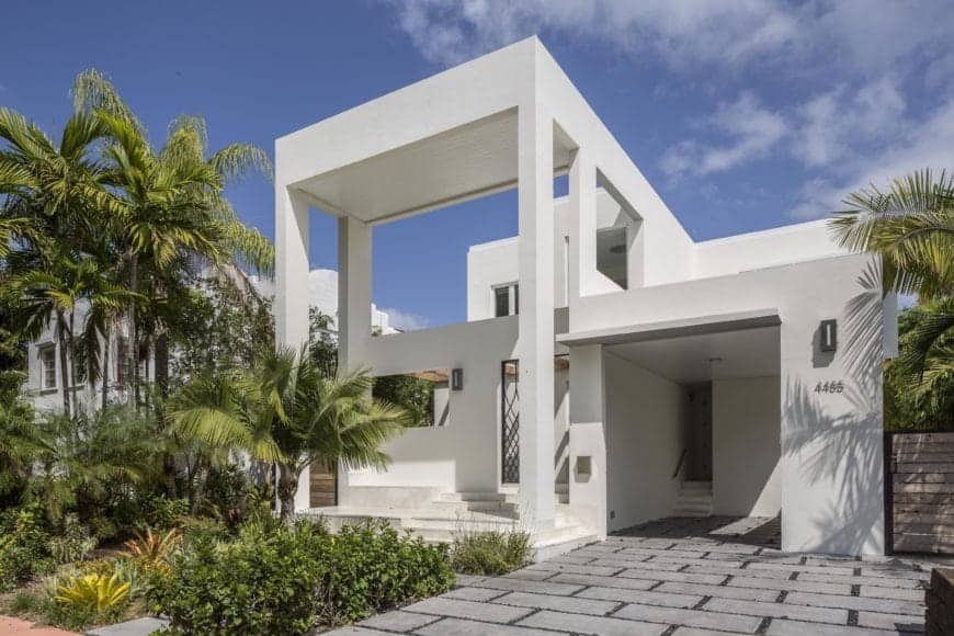 Pristine white modern house with a linear structure, multi-layered facade with soaring roof extension over the outer wall and a concrete driveway. Palm trees and tropical plants softened the sleek exterior.