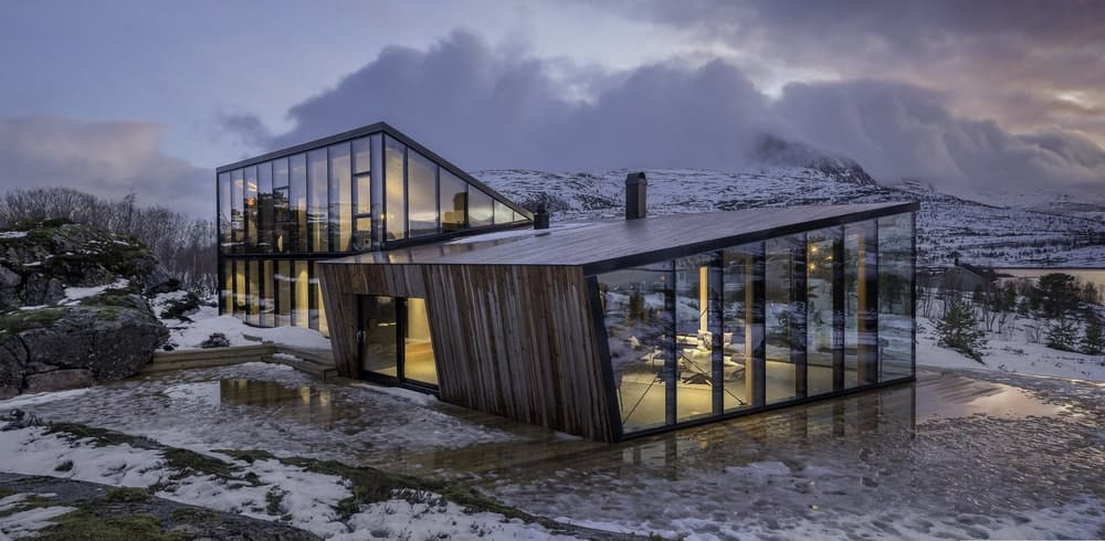A cutting edge house showcasing two volumes both with structural glazing which provides a panoramic view of the dramatic mountains.