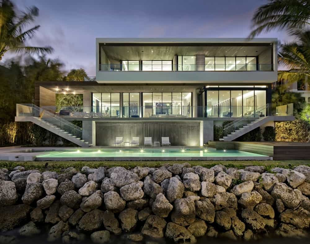 A modern house boasting a minimalistic design that sits on top of stone retaining walls. It has spacious balconies and concrete staircases on both ends leading down to the serene swimming pool.