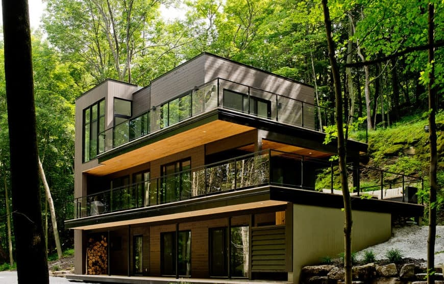 A three-story house with modern architecture featuring wood cladding, black metal framing and large glazed windows. It includes a wraparound patio and two spacious terraces enclosed in glass railings.