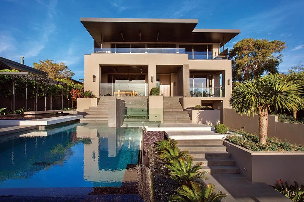 A modern house that's fully integrated with its surroundings. It's exterior has sharp structural design accompanied by a resort-style garden that features tiered landscaping and a stunning infinity pool.