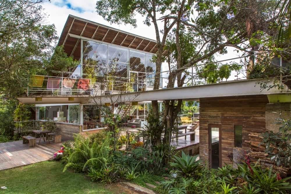 This charming home incorporates the modern aesthetics of its tall glass walls and metal beams to its natural landscaping filled with tall trees, various shrubs, flowering plants grass lawn. It has outdoor dining areas and sitting areas whereas to enjoy the surrounding landscape.