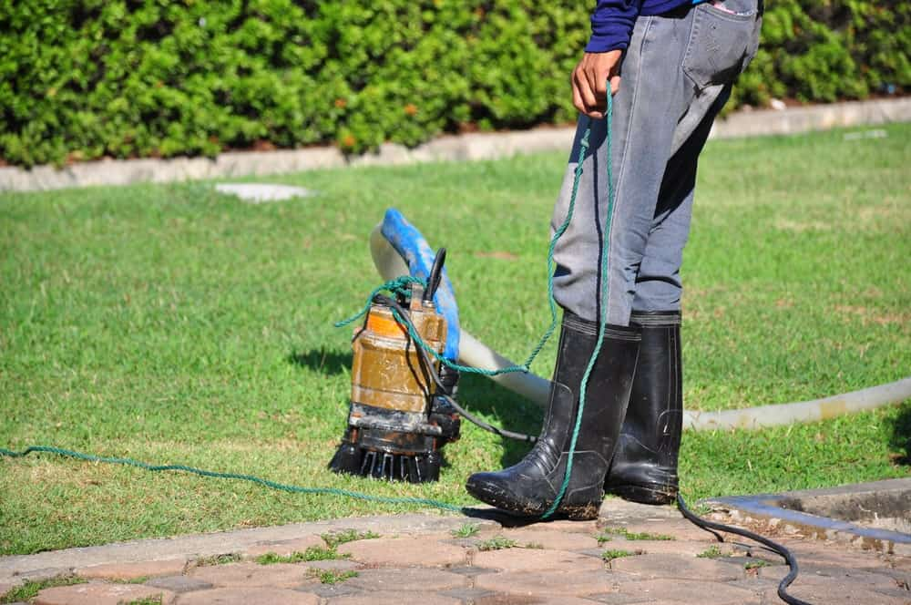 A sump pump being used out on the garden grass lawn.