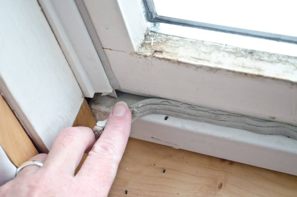 A grey caulk in old window casement with bare wood windowsill for winterizing to keep out cold drafts.