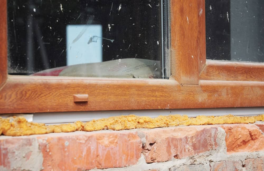 Installing plastic window in brick house with caulking gun foam insulation.