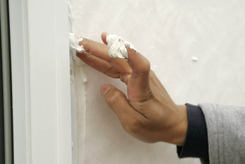 A hand applying caulk to the window's edge.