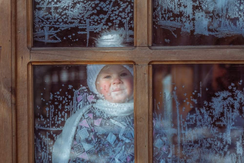 A child behind an icy window on a cold winter day.