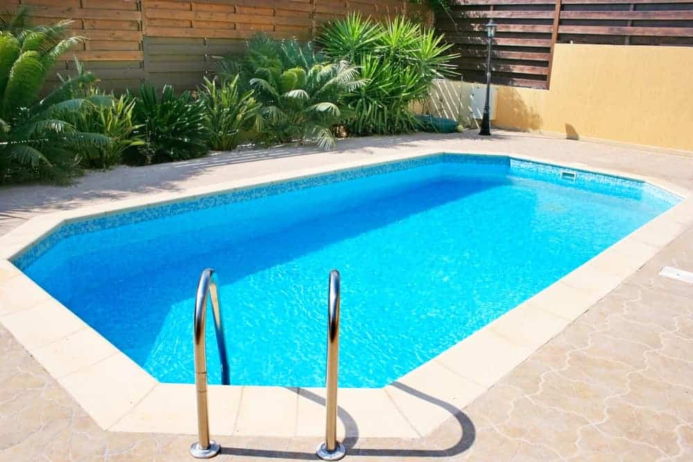 An in-ground swimming pool with chrome handrails and puzzle paving.