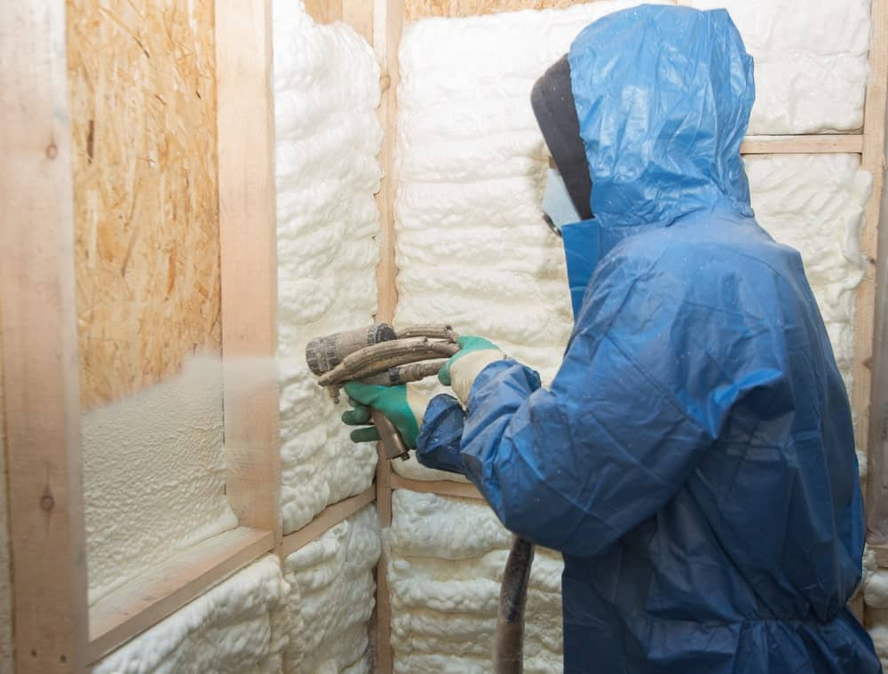 Man applying an insulating foam to the wall of the house.