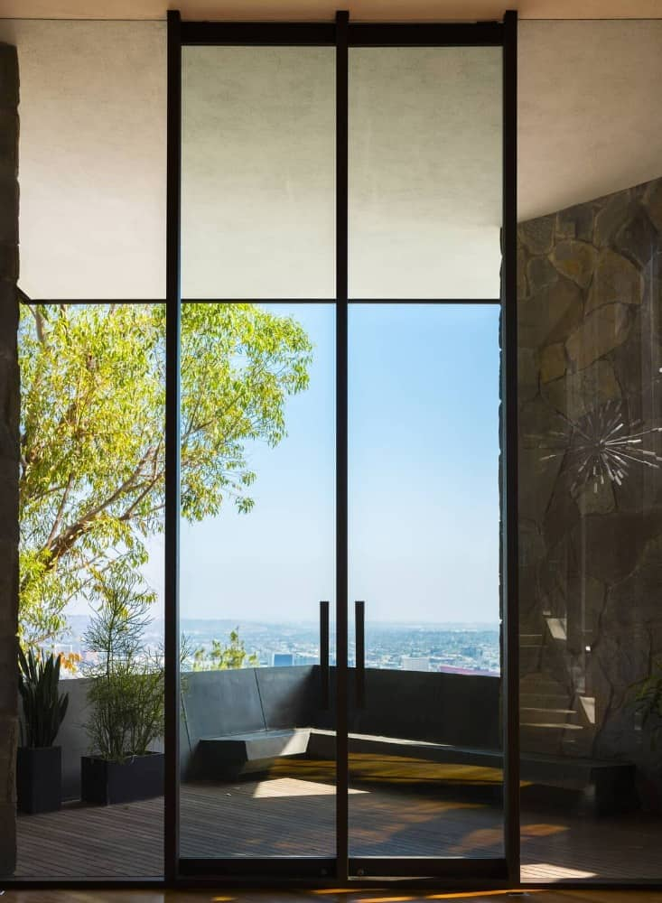The home has a tall glass doorway leading to the balcony area overlooking the stunning city. Images courtesy of Toptenrealestatedeals.com.