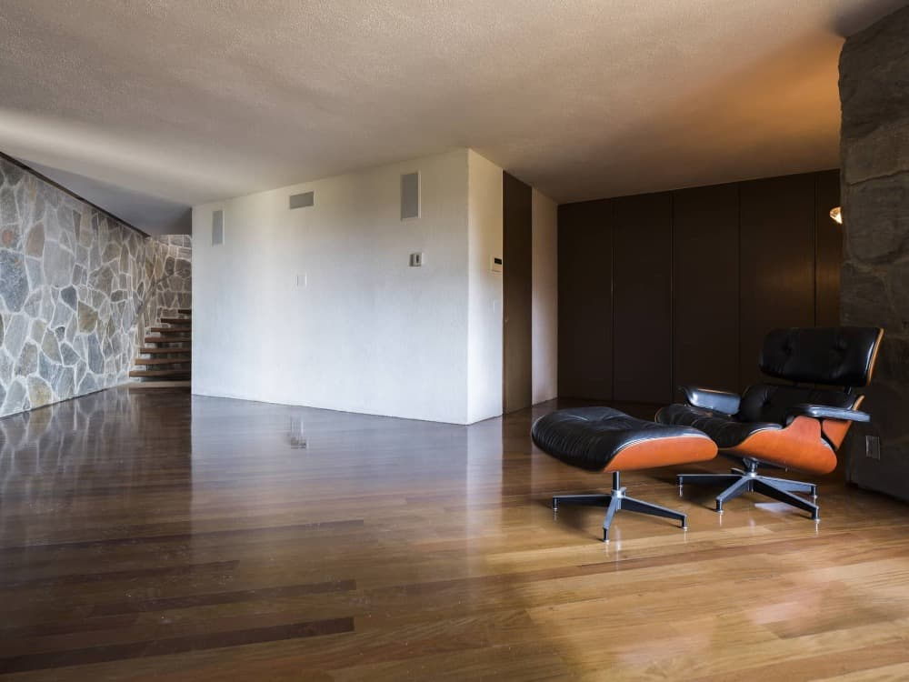 A look at this room's modern chair paired with a footrest. The house features stylish walls and well-polished hardwood floors. Images courtesy of Toptenrealestatedeals.com.
