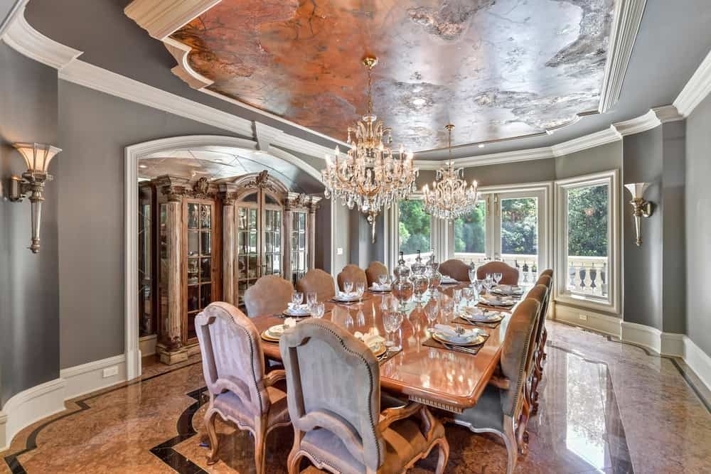 The home offers a large dining room boasting a large and elegant dining table and chairs set lighted by two fancy chandeliers hanging from the decorated ceiling. Images courtesy of Toptenrealestatedeals.com.