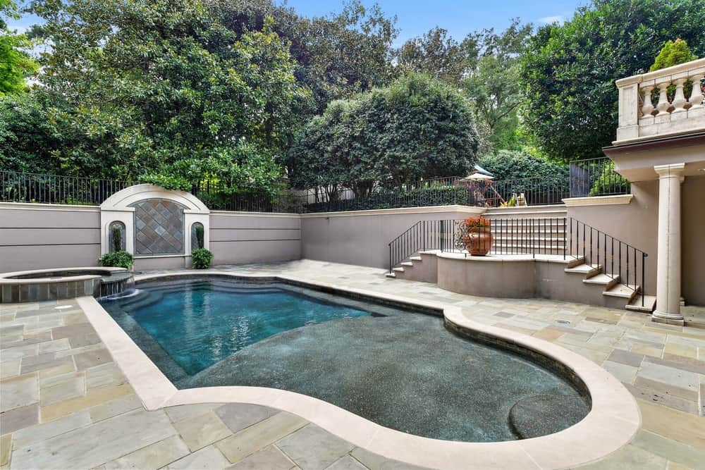 The swimming pool is set on the backyard with its own area. It is surrounded by the property's greenery. Images courtesy of Toptenrealestatedeals.com.