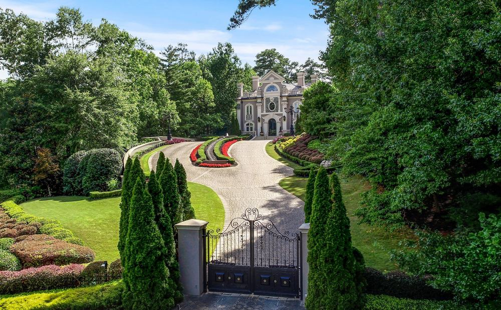 The view of the property's gorgeous house architectural and landscaping design. The property is gated and has a lush garden and beautiful walkway. Images courtesy of Toptenrealestatedeals.com.