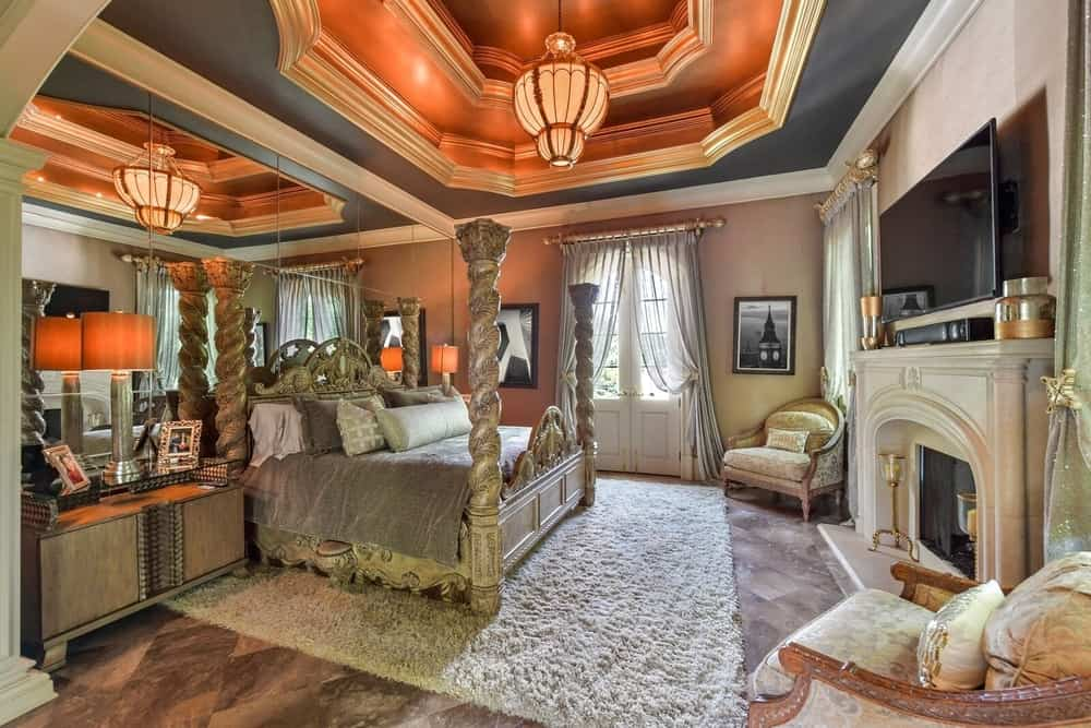 The primary bedroom suite offers a luxurious bed set along with a large fireplace and a flat-screen TV set in front. The room also features a stunning tray ceiling. Images courtesy of Toptenrealestatedeals.com.