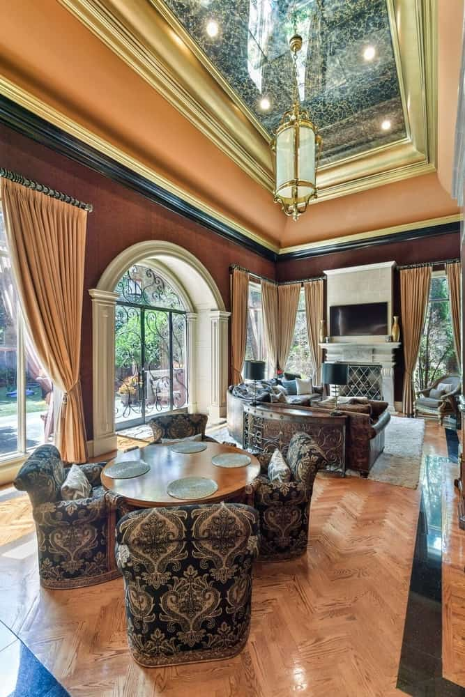 The formal living room offers a luxurious living set up with a fireplace and a flat-screen TV set in front, along with a round dining nook placed behind. Images courtesy of Toptenrealestatedeals.com.