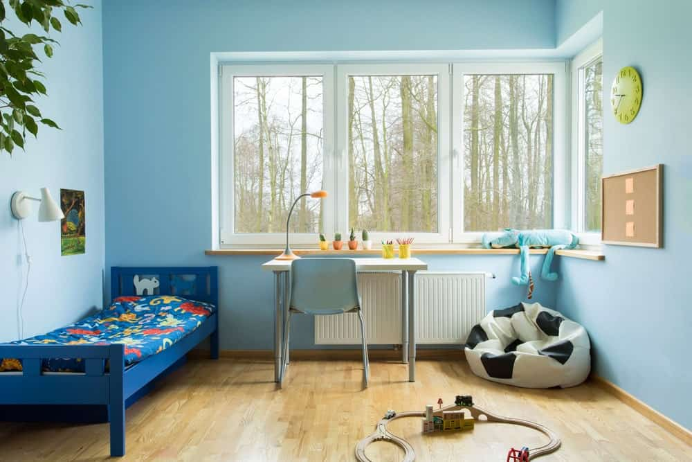 Kids bedroom with sky blue walls, hardwood flooring, glazed windows, blue bed, white desk and chair, wall clock and board, white sconce and a soccer ball bean bag.