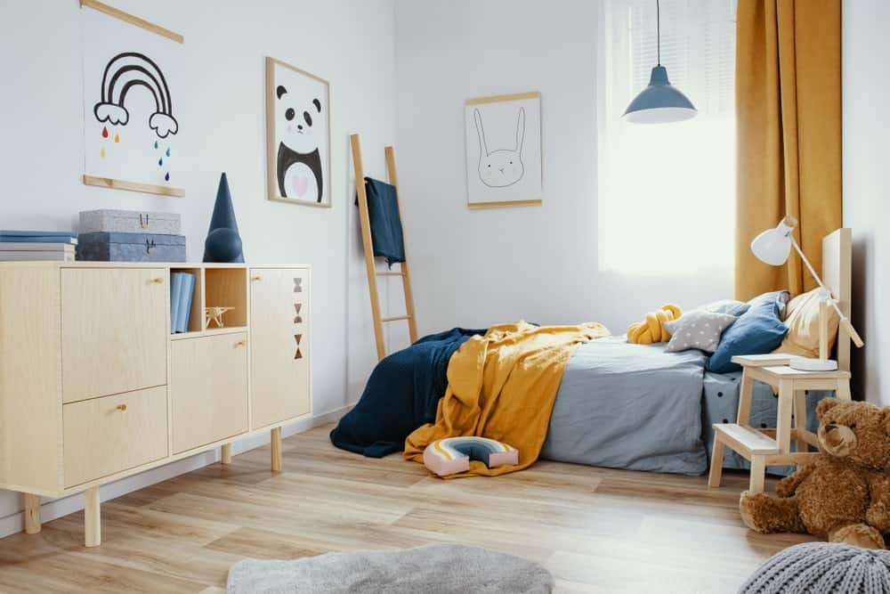 Kids bedroom with wide plank flooring, white walls, light wood dresser, comfy bed, pendant light, ladder and cute posters.