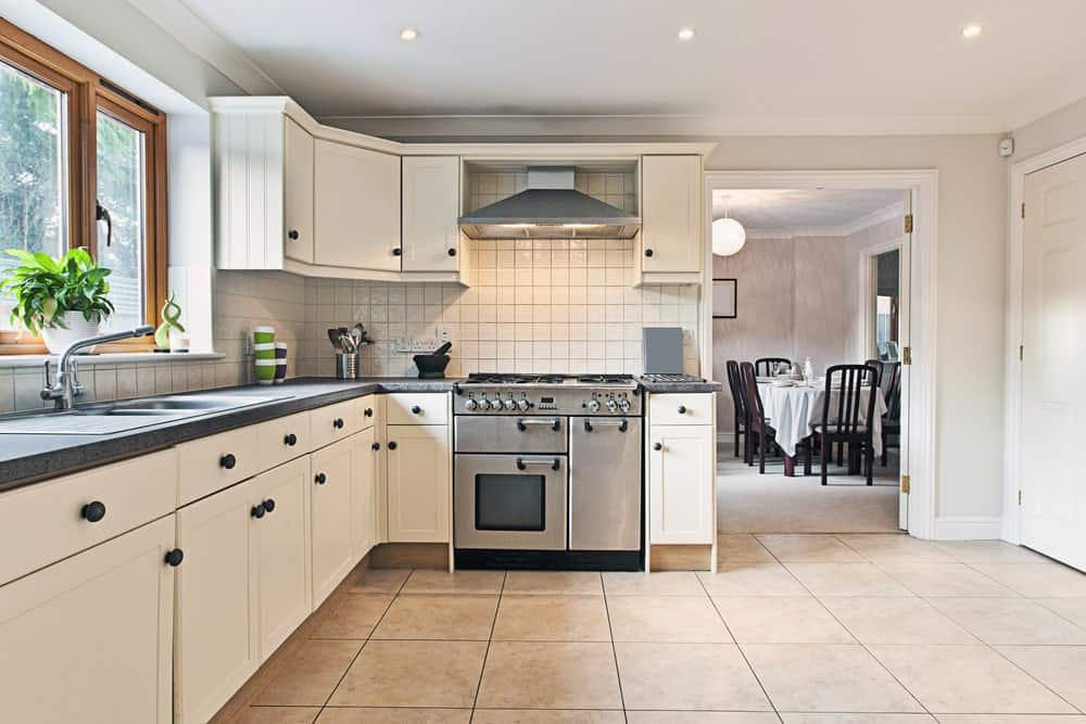Light and airy kitchen in average size with white cabinetry fitted with black knobs, stainless steel appliances, granite countertops, tiled flooring and wooden framed windows.