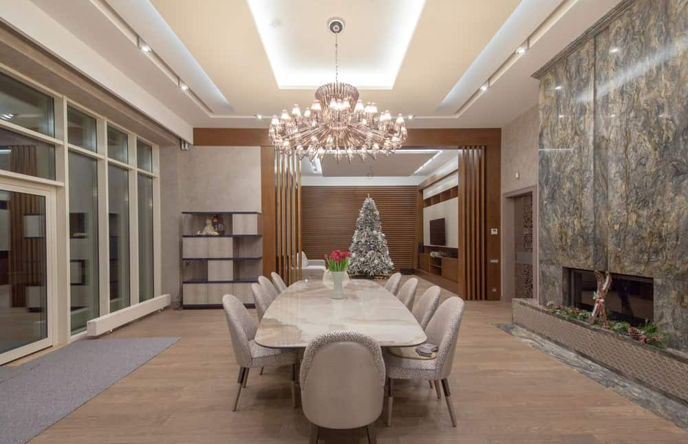 Large dining room with a modern fireplace fitted on the marble accent wall, a grand chandelier that hung from the tray ceiling, light hardwood flooring and a large marble dining table paired with beige round back chairs.