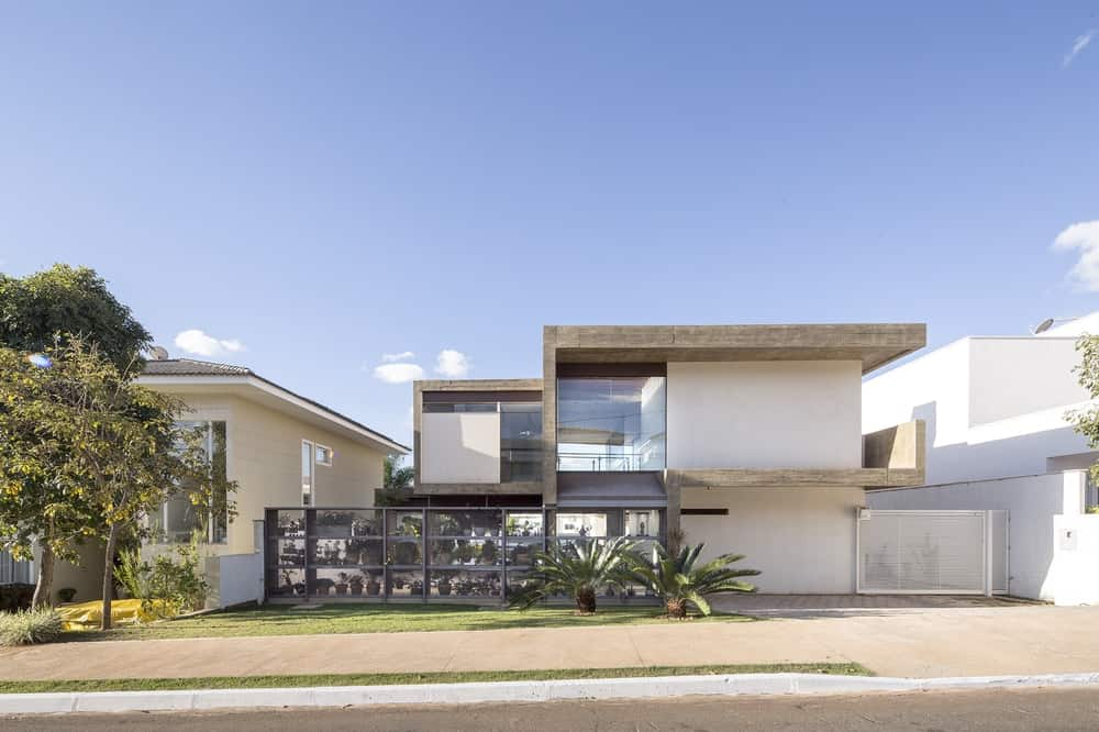 A large modern home designed by CoDA arquitetos. It has a white finished exterior with glass windows and walls. It also has a gated garage and a nice driveway.