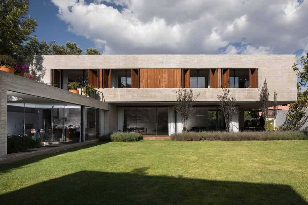Large and contemporary house designed by rdlp arquitectos. It features glass walls and windows, along with a wide and well-maintained lawn and garden area.