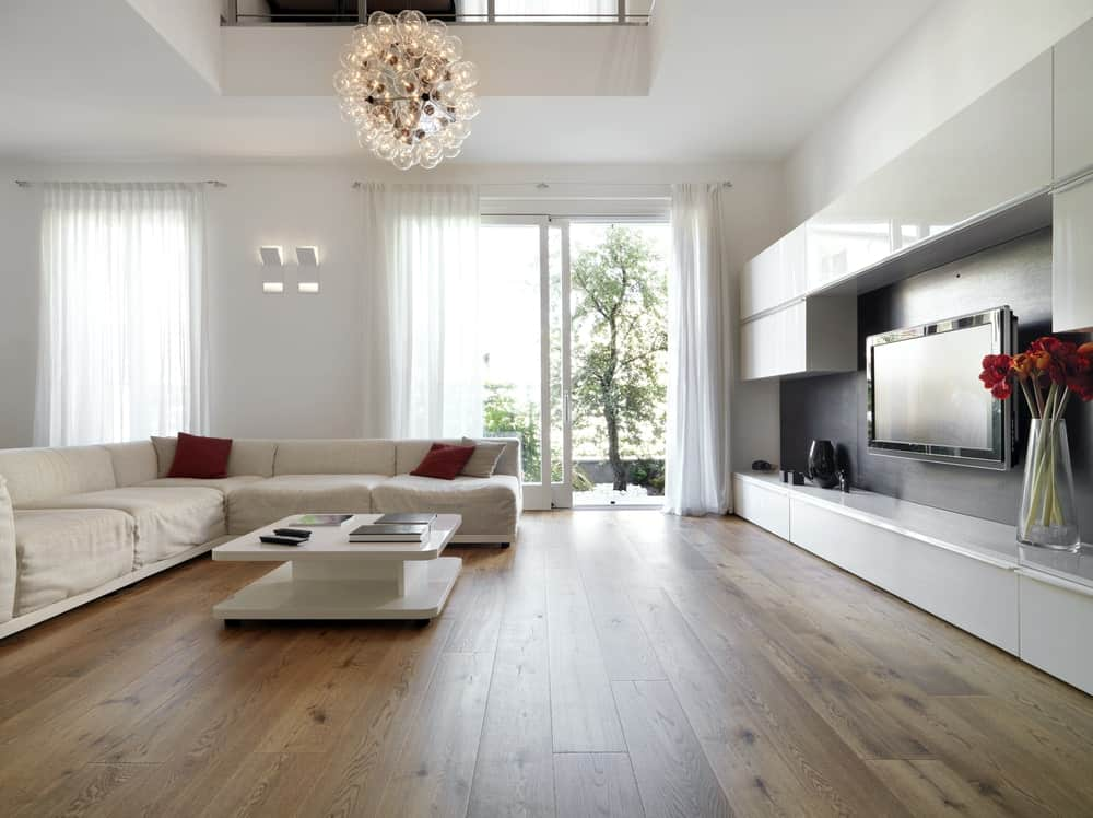 Large living room with white walls, wide plank flooring, sectional L-shaped sofa, glass globe lighting, modern coffee table, wall TV surrounded by high gloss cabinets and full height windows covered in sheer curtains.