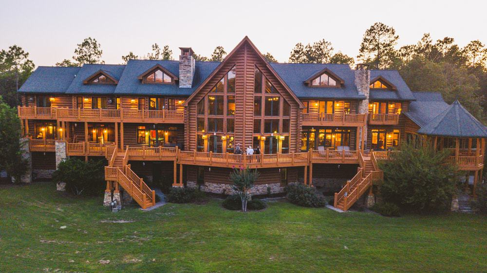 Stunning log house with a modish blue roof and multiple glass windows, along with warm interior lighting.