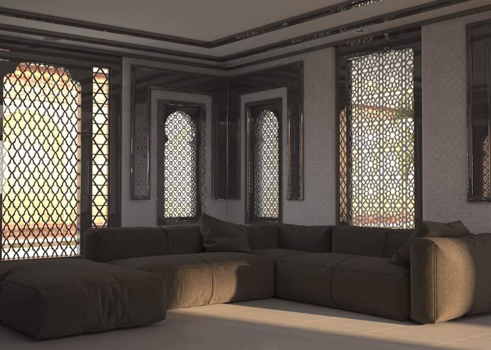 Living room interior with ornate window grills and a corner angular sectional sofa.