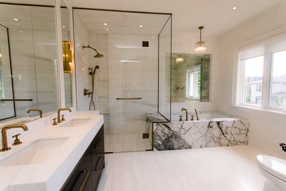 White primary bathroom with a dual sink vanity, walk-in shower marble bathtub, brass fixtures, tiled flooring, a toilet, framed windows and ambient lighting.