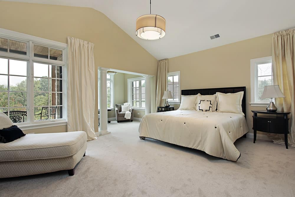 Spacious primary bedroom with carpet flooring, beige walls, white framed windows, comfy chaise lounge, sitting area, dark wood furniture, and a drum chandelier.