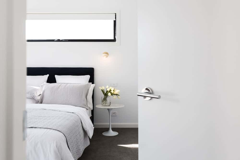 White door with chrome handle opening to a luxury primary bedroom.