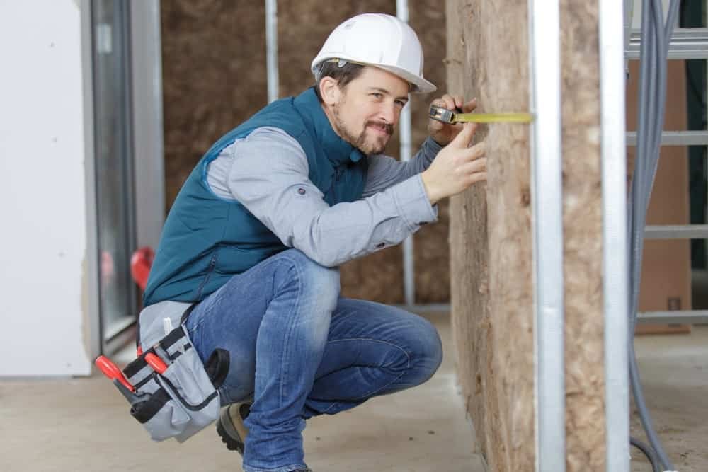 Man measuring insulated wall.