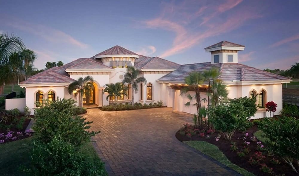 The stunning Mediterranean-style home has simple white exterior walls and warm light gray roof that seems to blend well with the sunset sky. There is a large walkway and driveway made of brick leading to the house that is surrounded by a large garden of tropical trees and flowering shrubs.