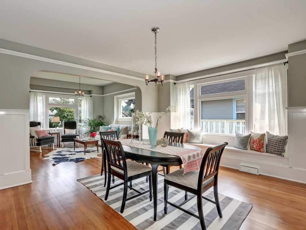 Medium dining room with oval dining table and cushioned chairs over a striped rug, gray walls clad with white wainscoting, a classic lighting and a window seat nook accented with printed throw pillows.