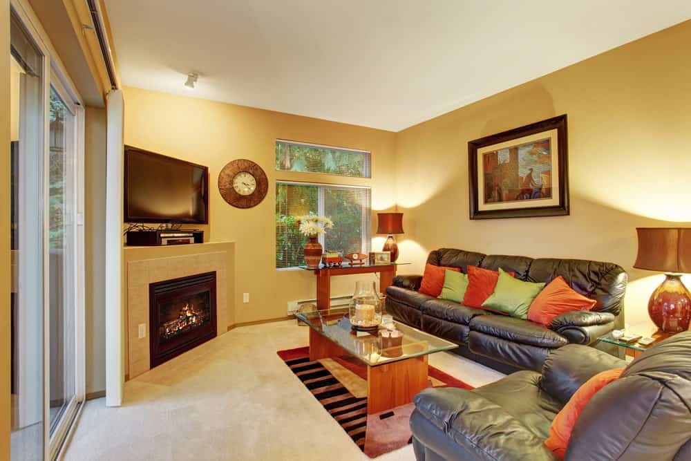 Medium-sized living room with yellow walls, beige carpet flooring, corner fireplace and TV, leather seats accented with colorful pillows, glass top tables, wall clock and a lovely artwork.