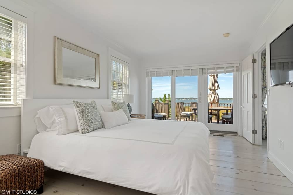 This large bedroom boasts a white bed setup with a large flat-screen TV on the wall in front. There's a doorway leading to the terrace too. Images courtesy of Toptenrealestatedeals.com.
