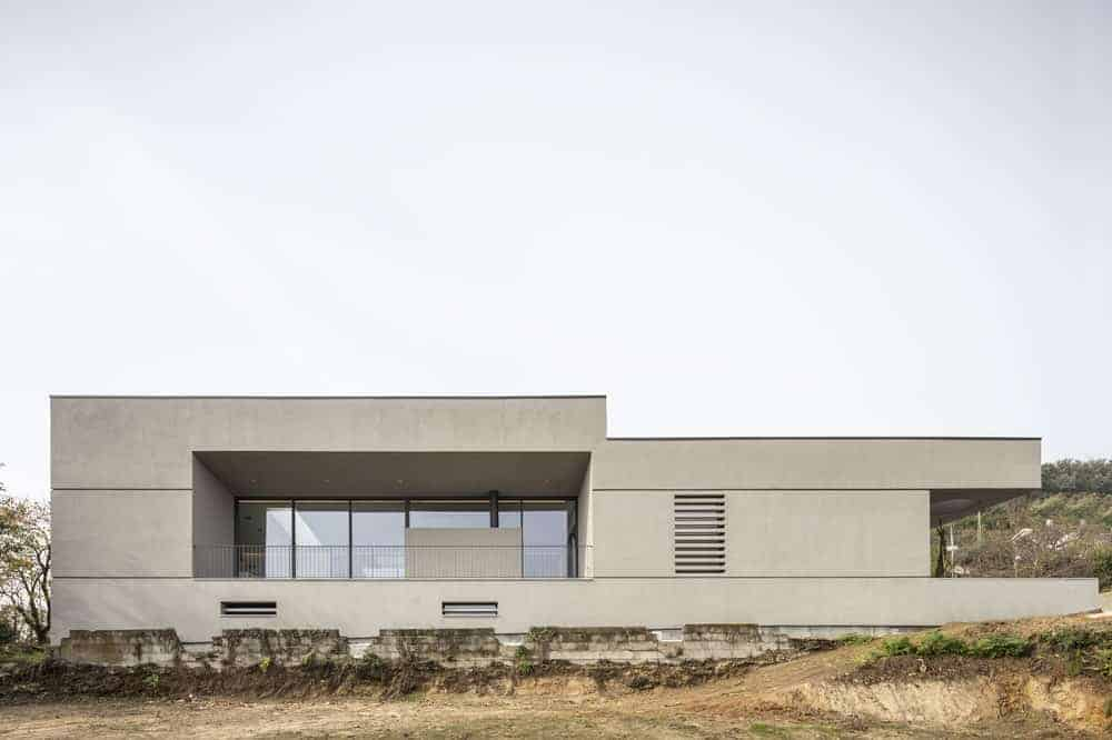 A modern house with minimalist designs in its interior and exterior. It also has a wide outdoor area along with glass windows and doors.