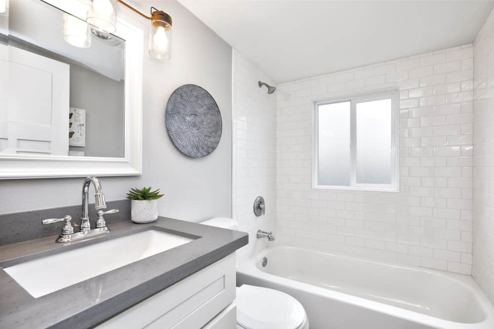 Modern bathroom with gray and white brick walls, sink vanity with granite countertop, glazed windows, toilet, tub and shower combo and white framed mirror illuminated by glass sconces.